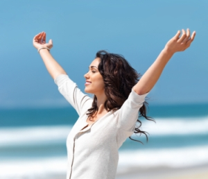 Pretty young woman with arms raised standing on beach