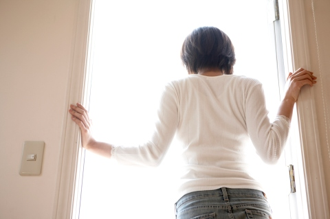 Yamanashi Prefecture, Japan. woman standing in doorway looking out at bright sunny day, view from behind and below